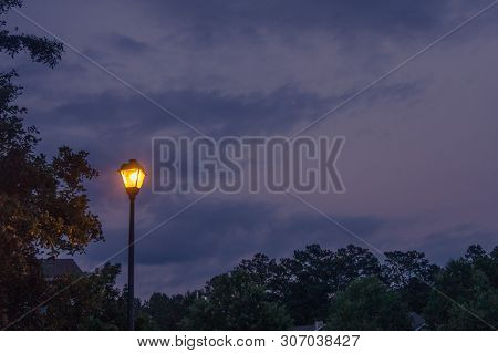Single Lone Street Light Lamp Post At Night Shining In The Dark In The Evening