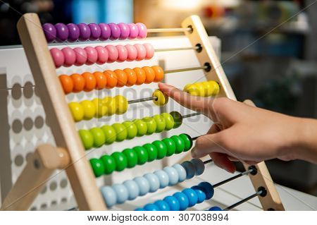 Male Hand Calculating With Beads On Wooden Rainbow Abacus For Number Calculation. Mathematics Learni