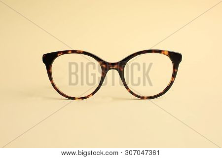 Modern Fashionable Acetate Spectacles, Torture Color Laying On Light Yellow Background.
