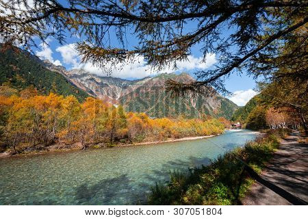 Blue River In Pine Forest Tree With Mountains Backgroud, Hiking In Kamikochi, Matsumoto, Japan