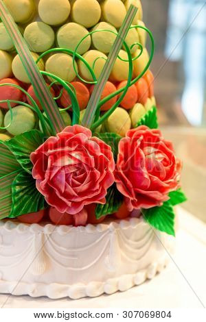 Detail of a beautiful celebration cake, decorated with pink and green macarons, edible sugar roses, leaves, tendrils and ribbons.