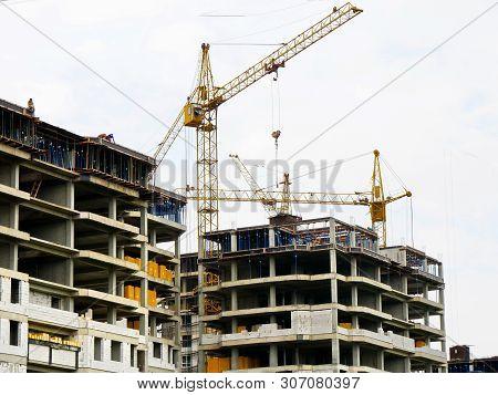 Construction Site. Building Site With Four Cranes. Concrete Buildings Under Construction.