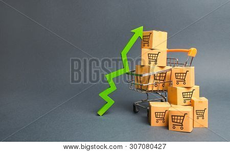 Shopping Cart With Cardboard Boxes With A Pattern Of Trading Carts And A Green Up Arrow. Increase Th