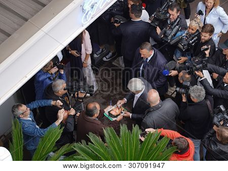 CANNES, FRANCE - MAY 19, 2019: Alain Delon gives autographs attends the photocall for Palme D'Or D'Honneur during the 72nd annual Cannes Film Festival
