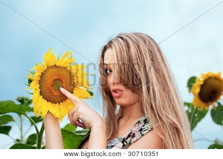 young beautiful woman between sunflowers in feld poster