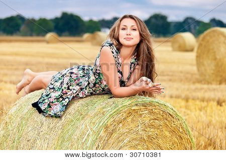 Woman  sitting on hay bale
