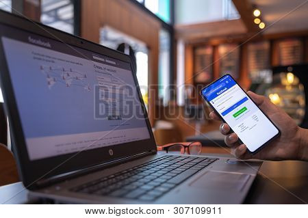 Chiang Mai, Thailand - May 01,2019: Man Holding Xiaomi Mi Mix3 With Facebook App On The Screen. Face