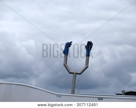 Two Blue Plastic Gloves On Metal Contraption On Fishing Boat In Southern Danish Harbour