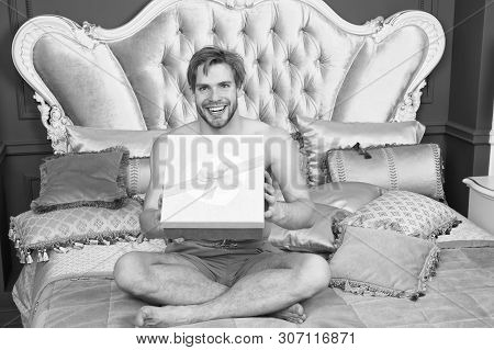 Already Found His Birthday Gift In Bed. Happy Man Holding Birthday Present Wrapped In Box. Sexy Man