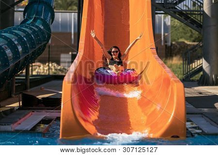 Happy Woman Coming Down On The Rubber Ring By The Orange Slide In The Aqua Park. Summer Vacation. We
