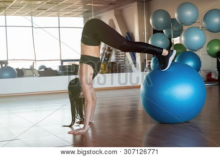 Young And Athletic Girl Using Fitness Ball In A Gym. Fitness Ball At Gym Workout Fitness And Pilates