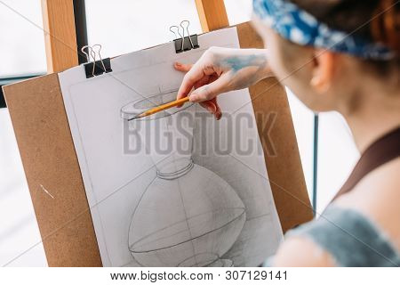 Art Studio. Closeup Side View Of Lady Measuring Proportions With Pencil In Drawing Vase.
