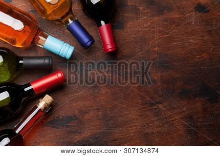 Various wine bottles on wooden table. Red, rose and white wines. Top view flat lay with copy space for your text