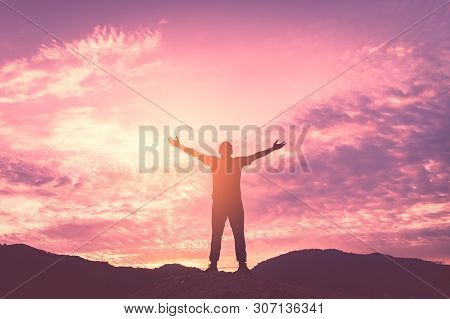 Backpacker Man Raise Hand Up On Top Of Mountain With Sunset Sky And Clouds Abstract Background. Copy
