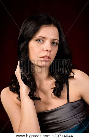 Beautiful young woman with a raised hand. The dark red background.