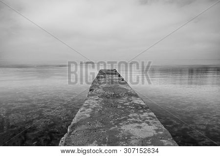 Wooden Jetty On Sea And Sky Reflection On The Water. Long Exposure And Black & White Photo