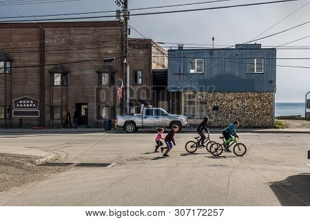 Nome, Alaska - June 8: Children Play And Ride Bicycles On The Historic Front St On June 8 2019 In No