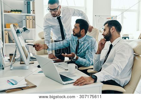 Putting Ideas Into Something Real. Group Of Young Modern Men In Formalwear Working Using Computers W