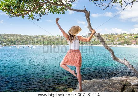 Happy Woman Dance Pirouette Beside Tree Leaning Out Over The Ocean  Wth Luxury Yachts Moored In The