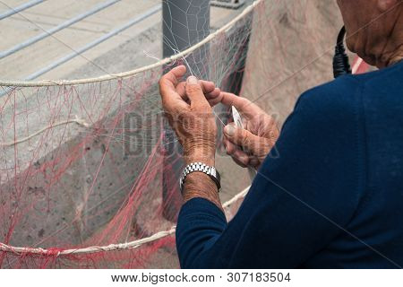 Old Fisherman Reparing Fishing Net, Sitting With Pipe In His Mouth.