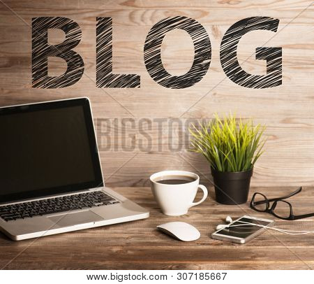 Blog text with computer keyboard, cup of coffee and plant pot. Wooden table background in vintage toned.
