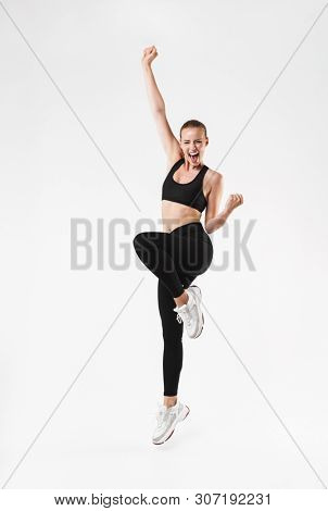 Full length image of delighted sporty woman wearing tracksuit rejoicing and clenching her fists isolated over white wall
