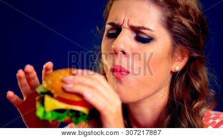 Girl close up eats cheeseburger. Take away fast food most popular food of youth.