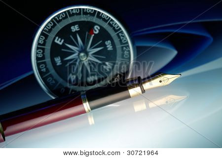 Pen with golden nib with compass and papers in the background