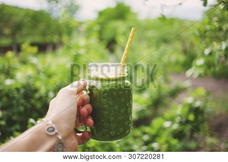 woman's hand holding a jar with green cold-pressed juice, nature background. Healthy eating, detoxing, juicing, body cleancing concept