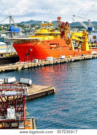 A Large Orange And Yellow Colored Offshore Construction Vessel (ocv) Is In A Dry Dock Of A Shipyard