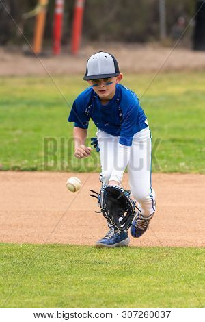 Youth Baseball Player In Blue Uniform Keeping Eyes On A Ground Ball Into His Glove In The Infield Du