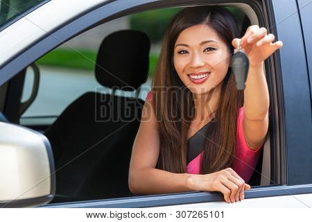 Beautiful Chinese Asian young woman or girl leaning out of a car in summer sunshine smiling with perfect teeth and long hair holding a car key. Car hire, driving test or vacation concept.