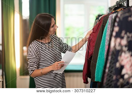 Focused Store Worker Wearing Stripped Sweater Checking Clothes On Hangers.