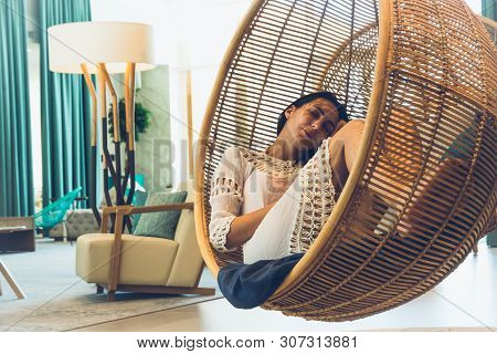 Woman sleeping in swing chair in beautiful home interior. Home decor design. Luxury home decor. Interior home decoration with swing chairs. Relaxing in beautiful home interior. Home decor.