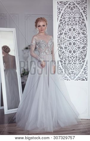 Beautiful Bride In Wedding Flowing Chiffon Dress Posing In Dressing Room With White Vintage Ornate C