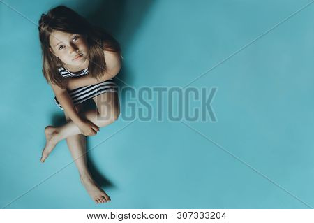 Girl Sitting On Plain Blue Background Looking At Camera. Child Glancing Up Top View. Simple Wallpape