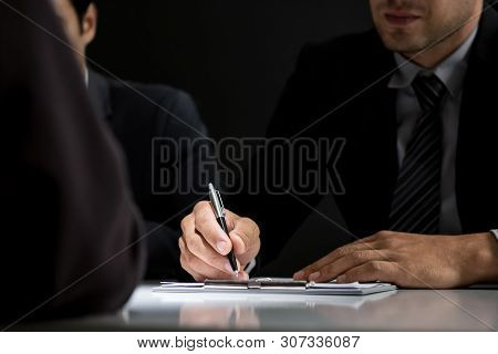 Interrogator Taking Note While Interviewing Suspect In The Interrogation Room
