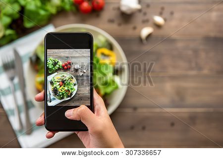 Food Blogger Using Smartphone Taking Photo Of Beautiful Mix Fresh Green Salad On Wood Table To Share