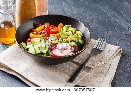 Vegan Buddha Bowl. Bowl With Fresh Raw Vegetables - Cherry Tomatoes, Cucumber, Radish, Avocado, Lett