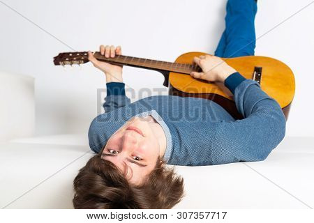 Happy Young Man Lying Back On Sofa With Guitar. Smiling Guitarist Relaxing On White Sofa. Close-up C