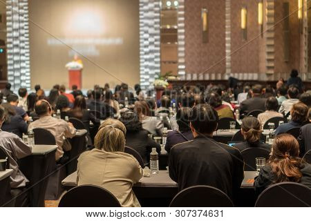 Rear View Of Audience Wearing And Listening Speakers Via Interpreter Headset On The Stage In The Con