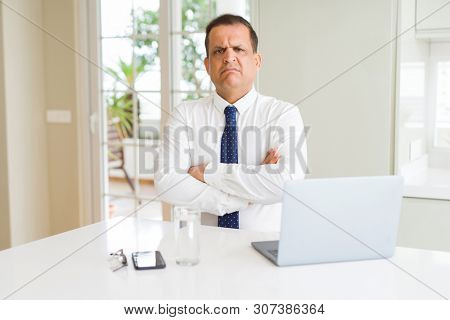 Middle age business man working with computer laptop skeptic and nervous, disapproving expression on face with crossed arms. Negative person.