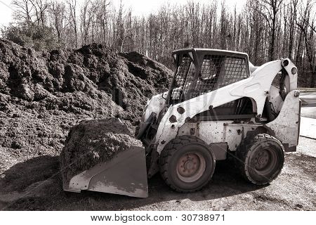Hydraulic Skid Steer Loader Machine At Mulch Pile