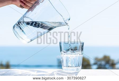 Purified Water Is Poured From A Glass Jug Into A Glass. The Concept Of A Healthy Lifestyle.