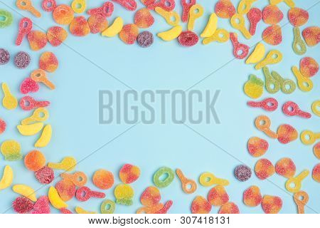 Blue paper background with sugary jellies and blank notepad. Place for your text. Cozy sweet background poster