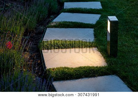Square Tile Marble Path Illuminated By A Lantern In The Backyard, A Winding Path In The Flowerbed Ga