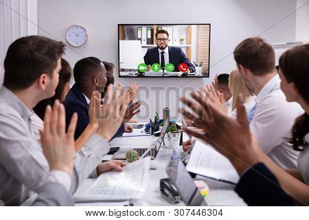 Group Of Businesspeople Having Video Conference With Another Business Team In Office