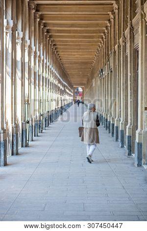 Paris, France - April 12, 2019 : Senior Woman With Beige Clothing Walking In The Palais-royal Colonn
