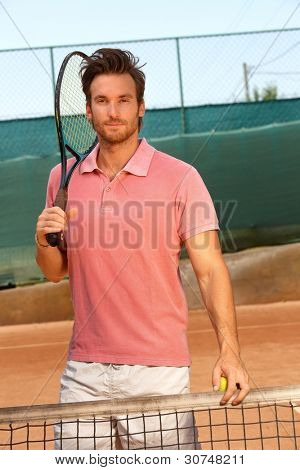 Handsome tennis player standing on hard court holding tennis racket.?