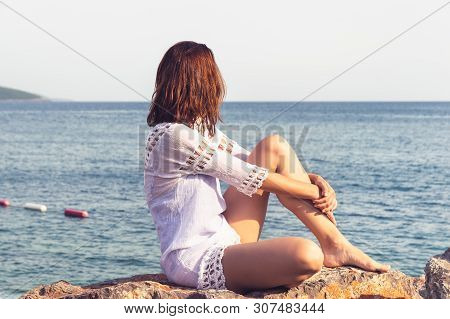 Traveler Girl Relaxing On Beach. Young Girl Traveler Relaxing In Vacation. Traveler Relaxing On Rock